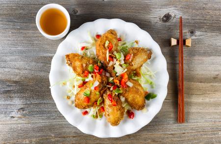 Vista superior de las alas de pollo al estilo asiático frito en un plato blanco con guarniciones. El té verde y palillos en el soporte. rústicas tablas de madera debajo. Foto de archivo - 50228692