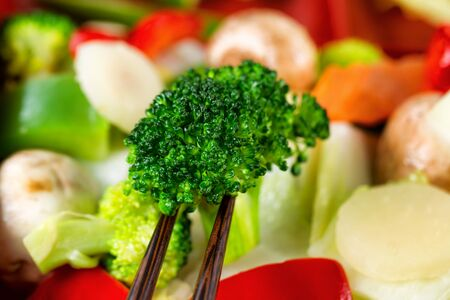 chinesisch essen: Freshly cooked vegetables with chopsticks. Filled frame format with selective focus on front broccoli between chopsticks.