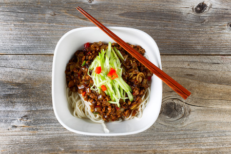 angled view: High angled view of noodles with ground beef and cucumbers. Chopsticks on top of bowl with rustic wood underneath.