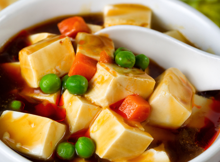 vegetable soup: Close up view of tofu, peas, and carrots in soup with spoon in bowl.