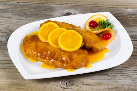tangy: Close up view of lemon chicken with tangy sauce and slice lemons on top in white plate with rustic wood underneath. Stock Photo