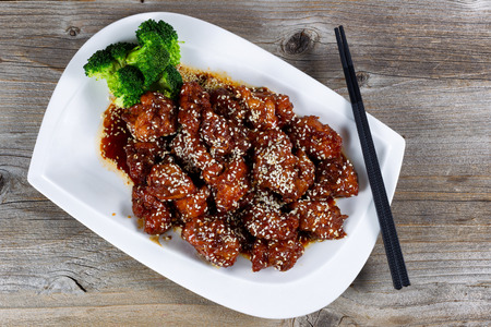 High angled view of Sesame seed chicken with broccoli. Chopsticks on plate with rustic wood underneath. Standard-Bild
