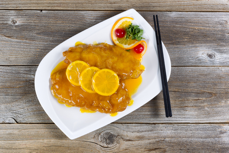 tangy: Top view of lemon chicken with tangy sauce and slice lemons on top in white plate with rustic wood underneath.