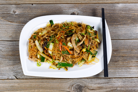 angled view: Angled view of cooked chicken strips and rice noodles with vegetables on rustic wood setting. Stock Photo