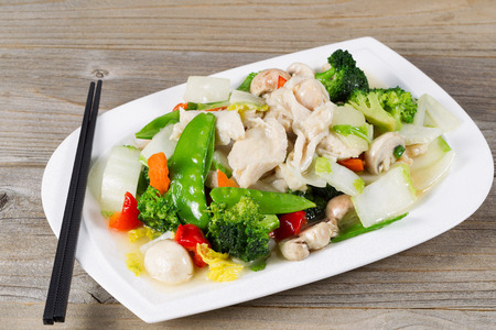 Close up view of stir fried white chicken pieces with broccoli, snow peas, peppers and mushroom in white plate on rustic wood setting.
