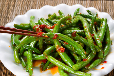 green bean: Close up view of spicy green beans with chopsticks in use. Selective focus on single bean being held by chopsticks. Stock Photo