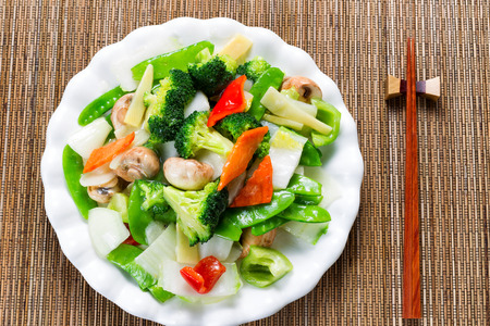 chinese meal: Top view of steamed mixed vegetables in large plate with bamboo mat underneath. Stock Photo