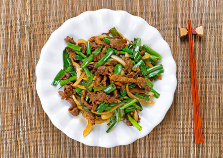 food dish: Top view of beef and green onions in white plate with bamboo mat underneath. Stock Photo