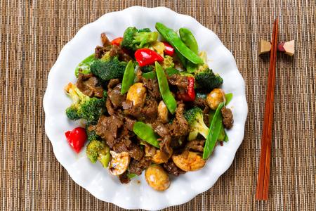 chinesisch essen: Erhöhte Ansicht der zarten Rindfleischscheiben, Champignons, Brokkoli, Paprika und Erbsen in der weißen Platte. Lizenzfreie Bilder