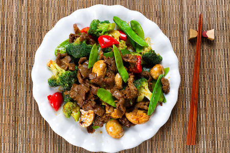High angle view of tender beef slices, mushrooms, broccoli, peppers and peas in white plate.
