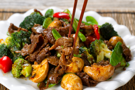 Close up view of tender beef slices, mushrooms, broccoli, peppers and peas in white plate. Selective focus on single piece held by chopsticks. Stockfoto