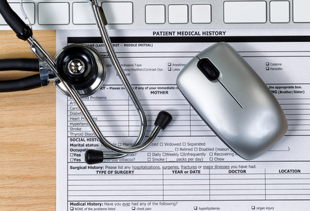 no name: Patient medical history form with stethoscope, computer keyboard and mouse on wooden desktop. Mouse and keyboard are nonfunctional no name brand items for display on desktops.