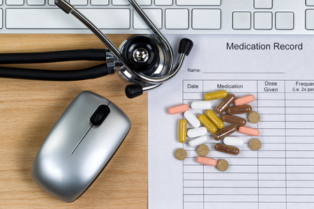 no name: Patient medication record form with stethoscope, pills, computer keyboard and mouse on wooden desktop. Mouse and keyboard are nonfunctional no name brand items for display on desktops.