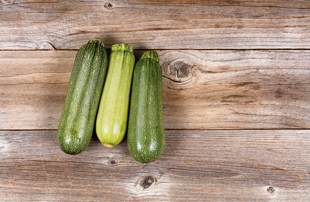 angled view: Whole cucumbers on vintage wood. High angled view.