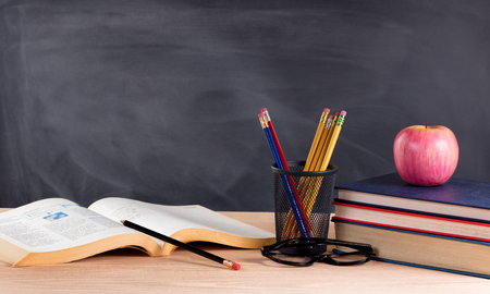 Bureau avec des livres, des crayons, des pommes, des lunettes de lecture et tableau blanc en arrière-plan. mise au point sélective sur la partie avant des objets de bureau. Banque d'images