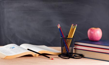 Desktop mit Bücher, Bleistifte, Apfel, Lesebrille und leere Tafel im Hintergrund. Selektiver Fokus auf vorderen Teil der Schreibtisch-Objekte. Standard-Bild