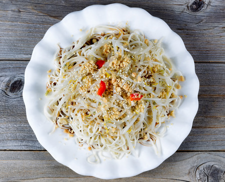 angled view: High angled view of Asian dish consisting of noodles, bamboo shoots, peppers and sesame seeds on rustic wood.