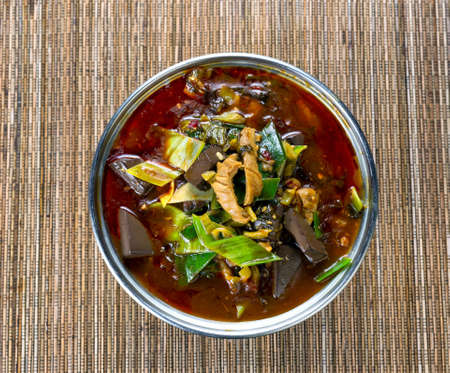 spicy cooking: High angled view of a cooking pot filled with vegetables, spicy pepper sauce and tofu for soup dinner on bamboo mat. Stock Photo