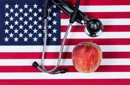 red america: United States of America flag with stethoscope and red apple. USA health concept. Overhead view in horizontal layout.