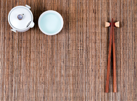 table setting: Overhead view of chopsticks, cup and tea server on bamboo mat. Stock Photo