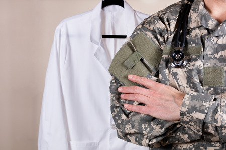 Close up partial view of medical doctor wearing military uniform and stethoscope with medical coat in background.