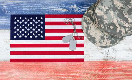 memorial day: Overhead view of United States of America national colors of red, white, blue on aging boards with military cap, USA flag and identification tags. Patriotic concept. Stock Photo