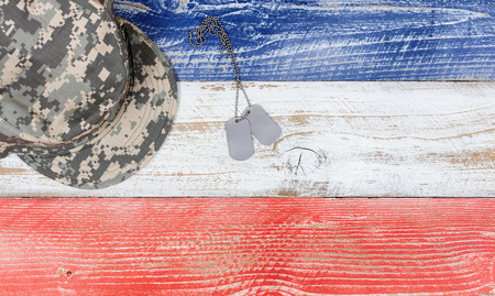 culture day: Overhead view of United States of America national colors of red, white, blue on aging boards with military cap and identification tags. Patriotic concept. Stock Photo