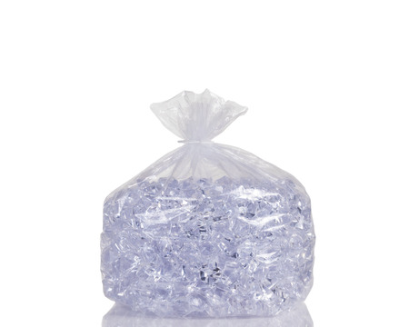 ice cold: Big of ice cubes in clear plastic bag isolated on white with reflection.