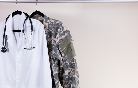 medical doctor: Medical Doctor Consultation white coat, stethoscope around collar, and military uniform hanging on rack. Off white wall in background. Horizontal layout with copy space. Stock Photo