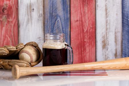 independencia: Vista frontal de un vaso de cerveza fr�a y oscura con un guante de b�isbol gastado, palo y bola. tablas de madera pintadas descoloridos rojo, blanco y azul de fondo con la bandera de EE.UU. debajo.