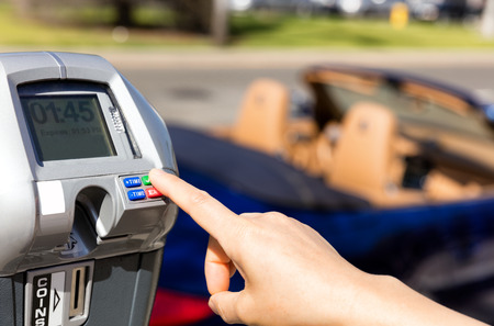 Close up of female hand, index finger, selecting parking meter time outdoors on street. Selective focus on tip of index finger and meter buttons. Stockfoto