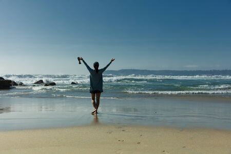 barefoot: Back view of a woman walking barefoot into ocean with arm raised towards bright sky. Stock Photo