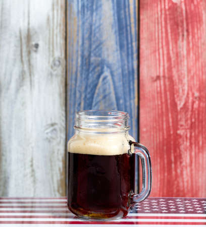 red white blue: Front view of a single jar glass of cold dark beer.  Faded wooden boards painted red, white and blue in background with USA flag underneath.