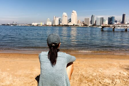 back bay: Back view of a woman sitting on beach and looking out into bay of San Diego, California.