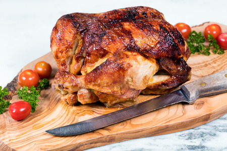 Close up front view of barbecued chicken with vegetables, herbs and large cutting knife on wooden server with white marble underneath. Selective focus on upper front leg of chicken.