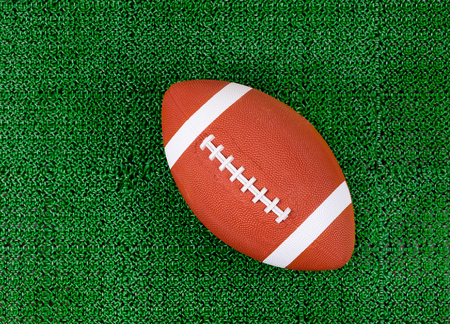 sport object: Overhead view of American football on artificial grass