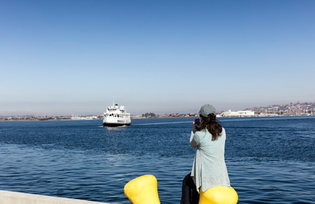 back bay: Back view of a woman taking photos with cell phone of San Diego bay in Southern California while sitting down at pier.