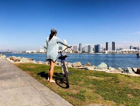 back bay: Back view of a woman, holding bicycle, will looking at the bay of San Diego in Southern California.