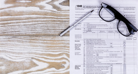 fading: Overhead view of tax form, pen, and reading glasses on fading white desktop. Stock Photo