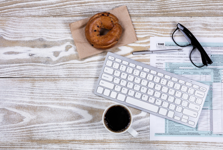 Overhead view of tax form, pen, keyboard, dark coffee, bagel and reading glasses.