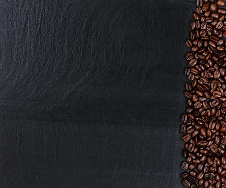 grano de cafe: Overhead view of roasted coffee beans on natural black slate stone. Plenty of copy space.