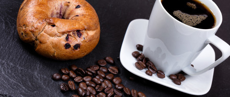 bagel: Angled view of roasted coffee beans on natural black slate stone with coffee drink and bagel in background. Selective focus on coffee beans in forefront.