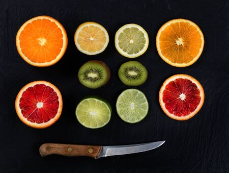 lemon slice: Overhead view of a variety of sliced citrus fruits and knife on black slate. Stock Photo