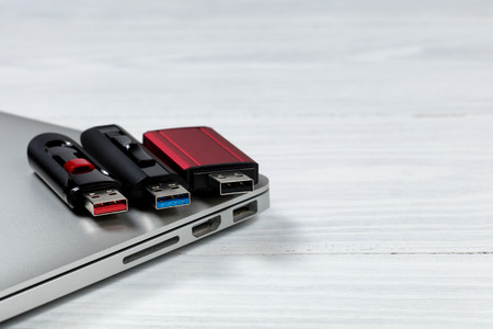 medium close up: Three thumb drives with different colors inside for USB technologies. Computer and desktop in background.