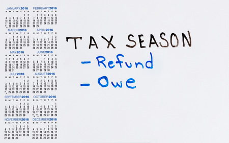owe: Calendar on white board with tax concept for either a refund or owe.
