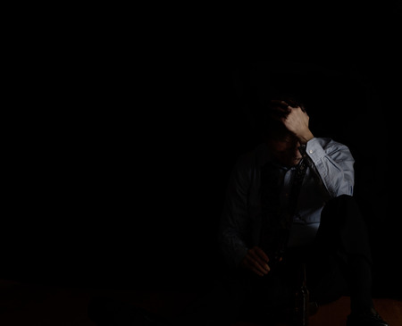 Depressed mature man holding head down while sitting on floor with beer in hand. Selective focus hand holding head of man. Depression concept.
