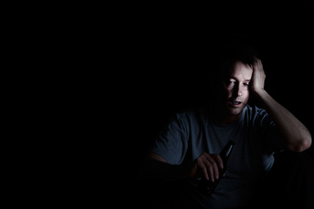 alcoholic man: Depressed mature man drinking in dark. Selective focus on face with light. Depression concept.