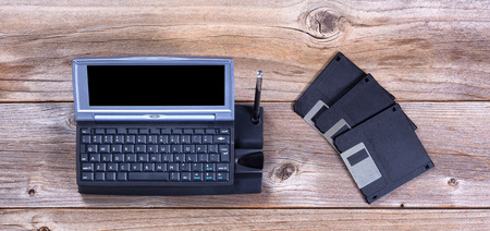 Overhead view of a vintage handheld computer on stressed wood with data diskettes.  Obsolete concept. 版權商用圖片 - 54113426