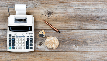 fossils: Overhead view of an adding machine and paper roll on stressed wood with stone fossils.  Obsolete technology concept. Stock Photo