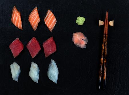 Overhead view of fresh Japanese sushi, ginger, wasabi, and chopsticks on black slate.